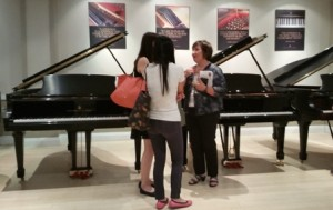 Piano consultant Janice Brisco (r) chats with guests